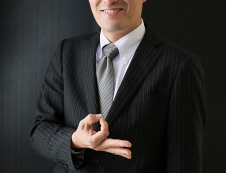 手でお金のマークを作るスーツ姿の男性